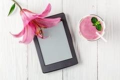 莓果圆滑的人用酸奶和ebook 库存照片