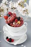 莓果在一个白色杯子的脆饼油炸圈饼 免版税图库摄影