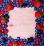 莓果在木背景构筑 草莓,蓝莓 免版税库存照片