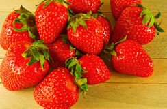 莓果是木表面上的大和成熟草莓 免版税库存照片