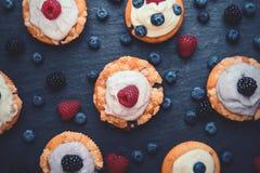 莓果杯形蛋糕顶视图与乳脂状的顶部的 库存图片