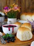 莓果果酱和金黄小圆面包 库存图片