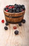 莓果莓和黑莓在木篮子 免版税图库摄影