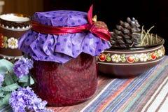莓果酱瓶子,在桌布, eco厨房的乌克兰黏土盘 免版税库存图片