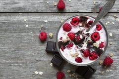莓点心用新鲜的莓果、巧克力、酸奶和格兰诺拉麦片与匙子 免版税图库摄影