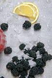 黑莓特写镜头与冰的和切片在一张潮湿桌上的傻的柠檬与水滴在灰色背景的 图库摄影
