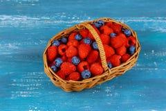 莓用在篮子的蓝莓在一个老蓝色委员会 库存图片