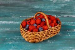 莓用在篮子的蓝莓在一个老蓝色委员会 免版税库存图片