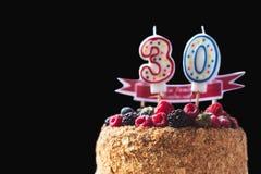 莓黑莓与蜡烛的生日蛋糕第30在黑背景和copyspace您的文本的 库存图片