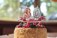 莓黑莓与蜡烛第30的生日蛋糕 免版税库存图片