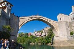 莫斯塔尔、波斯尼亚&黑塞哥维那- 2017年10月:游人在莫斯塔尔观看一个人跳从在Neretva河的著名老桥梁, 库存图片