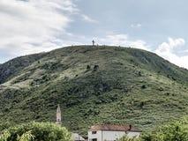 莫斯塔尔,波黑- 2014年5月1日:十字架在莫斯塔尔顶部小山  库存图片