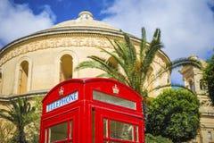 莫斯塔,马耳他-有棕榈树的传统英国红色电话亭和在背景的著名莫斯塔圆顶 库存照片