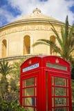 莫斯塔,马耳他-有棕榈树的传统英国红色电话亭和在背景的著名莫斯塔圆顶 免版税库存图片