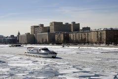 莫斯科河堤防的冬天视图和巡航乘快艇在被冰的水的航行 免版税库存图片