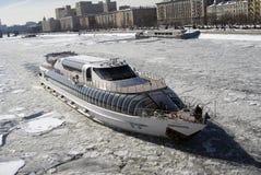 莫斯科河堤防的冬天视图和巡航乘快艇在被冰的水的航行 库存图片