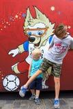 莫斯科街道欢乐背景在世界杯的2018年 世界杯的标志背景的两个兄弟在红场的 库存照片
