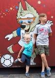 莫斯科街道欢乐背景在世界杯的2018年 世界杯的标志背景的两个兄弟在红场的 免版税库存照片