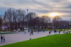 莫斯科,俄罗斯2018年4月, 24日:室外观点的人是乘坐,滑冰和走在高尔基公园附近, suring日落 库存照片