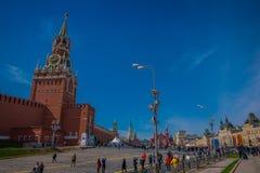 莫斯科,俄罗斯2018年4月, 24日:走接近克里姆林宫鸣响的时钟的室外观点的未认出的人民  库存图片
