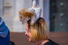 莫斯科,俄罗斯2018年4月, 24日:未认出的年轻白肤金发的妇女站立在有一只鸽子的一条街道在她的头,美好 库存照片