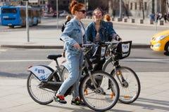 莫斯科,俄罗斯- 2018年4月30日:一个小组两个女孩站立与在边路的租用的自行车 首都中心 库存图片