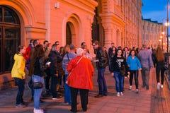莫斯科,俄罗斯- 2018年4月30日:与一个小组的一个指南游人临近圣蓬蒿红场的` s大教堂 在sunsetn前 库存图片
