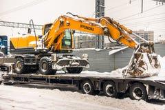 莫斯科,俄罗斯- 2018年2月05日:专业强有力的卡车运输在一辆lowboy拖车的黄色轮子挖掘机现代 免版税库存图片