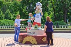 莫斯科,俄罗斯- 2018年6月03日:世界杯足球赛俄罗斯2018年狼的正式标志背景的走的游人Zabivaka  免版税库存图片