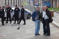 莫斯科,俄罗斯- 2018年4月30日:人们在警察和Rosgvardia前面站立在封销线在一次集会以后在萨哈罗夫大道 免版税库存图片