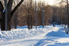 莫斯科,俄罗斯- 2018年3月20日:妇女走与太阳光芒照亮的一个积雪的公园胡同的一个小孩子 免版税库存照片