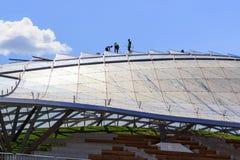 莫斯科,俄罗斯- 2018年6月03日:工作者在sunn的Zaryadye公园执行一个大圆形剧场的玻璃屋顶的维护 图库摄影