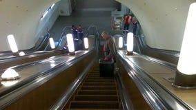 莫斯科,俄罗斯- 2018年9月16日:带着手提箱的一个人陷入工作者修理自动扶梯栏杆的地铁 影视素材