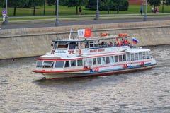 莫斯科,俄罗斯- 2018年6月19日:有漂浮在Moskva河的堤防背景的游人的游船一个多云总和的 图库摄影