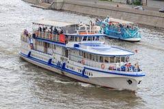 莫斯科,俄罗斯- 2018年6月19日:有漂浮在Moskva河的堤防背景的游人的游船多云su的 免版税库存图片
