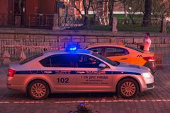 莫斯科,俄罗斯- 2018年4月30日:有闪光灯和一辆出租汽车的一辆警车在圣蓬蒿红场的` s大教堂附近 库存图片