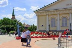 莫斯科,俄罗斯- 2018年6月03日:游人在世界杯足球赛俄罗斯的正式标志背景拍摄了2018年在Manezhn 免版税图库摄影