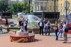莫斯科,俄罗斯- 2018年6月03日:游人在世界杯足球赛俄罗斯2018年狼的正式标志背景拍摄了Zabiva 免版税图库摄影