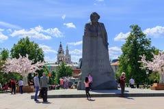 莫斯科,俄罗斯- 2018年6月03日:游人在纪念碑背景中拍一张照片给革命正方形的卡尔・马克思 图库摄影
