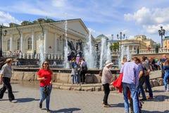 莫斯科,俄罗斯- 2018年6月03日:游人在Manezhnaya广场走反对莫斯科Manege喷泉和大厦在晴朗的夏天 免版税库存图片