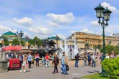 莫斯科,俄罗斯- 2018年6月03日:游人在Manezhnaya广场走在四个季节喷泉喷泉附近在晴朗的夏天早晨 免版税库存图片