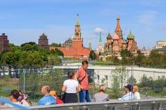 莫斯科,俄罗斯- 2018年6月03日:游人坐在一座浮桥的一条长凳在克里姆林宫背景的Zaryadye公园  库存图片