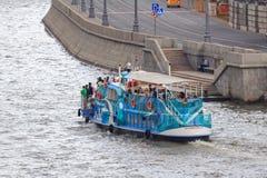 莫斯科,俄罗斯- 2018年6月19日:漂浮与Moskva河的堤防背景的游人的游船一个多云总和的 免版税库存图片