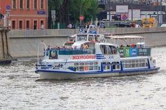 莫斯科,俄罗斯- 2018年6月19日:漂浮与Moskva河的堤防背景的游人的游船一个多云总和的 库存照片