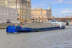 莫斯科,俄罗斯- 2018年6月21日:漂浮反对Moskva河堤防的被装载的驳船在一个晴朗的夏日 免版税库存照片