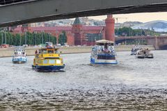 莫斯科,俄罗斯- 2018年6月19日:漂浮在Moskva河的桥梁下的游船克里姆林宫背景的a的 免版税库存图片