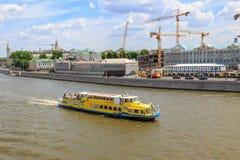 莫斯科,俄罗斯- 2018年6月03日:漂浮在Moskva河的Sofiyskaya堤防背景的黄色游船晴朗的 库存图片