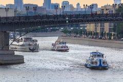 莫斯科,俄罗斯- 2018年6月19日:漂浮在Patriarshiy桥梁背景的Moskva河的游船在一个多云夏天e 库存照片