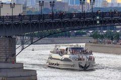 莫斯科,俄罗斯- 2018年6月19日:漂浮在Patriarshiy桥梁背景的Moskva河的游船在一多云夏天ev的 库存照片