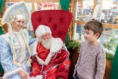 莫斯科,俄罗斯- 2018年12月1日:男孩在他的中央儿童的商店、新年和平安夜的房子里会见圣诞老人 免版税库存图片